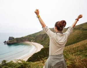 woman standing on hillside looking at ocean with hands in air, victorious
