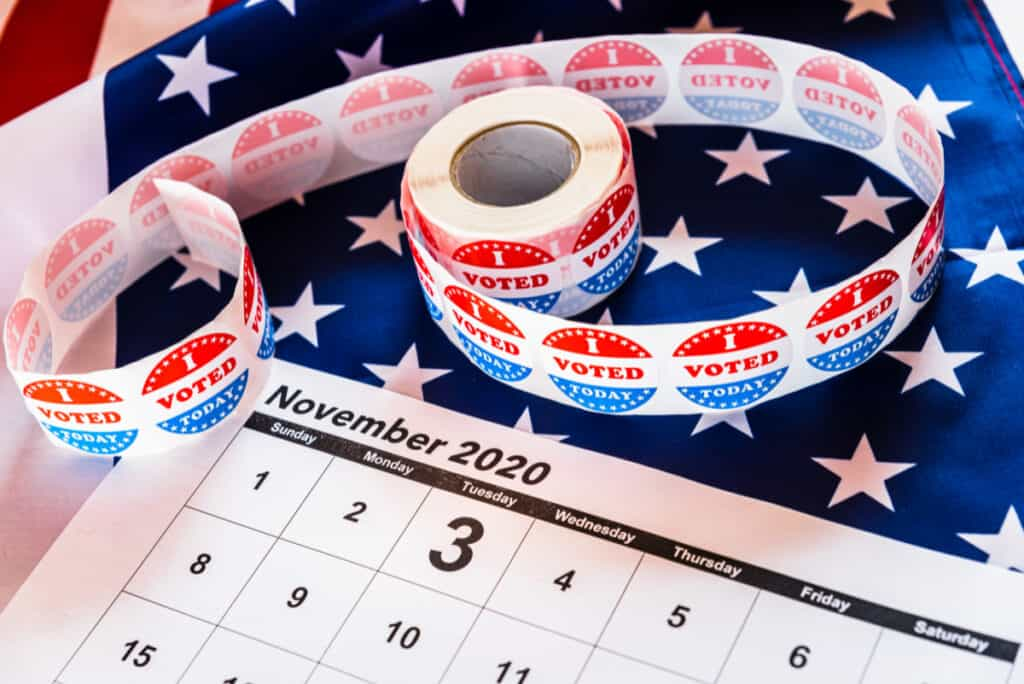 I Voted stickers on American flag, with calendar of November and election day circled