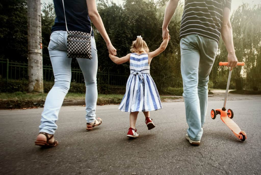 parents walking with little girl in between them, holding hands